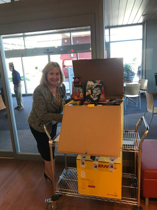 Dianne standing next to an open box of donated LEGO sets