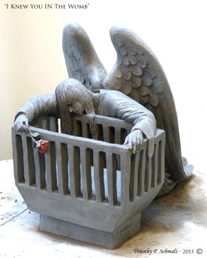Angel leaning over an empty cradle