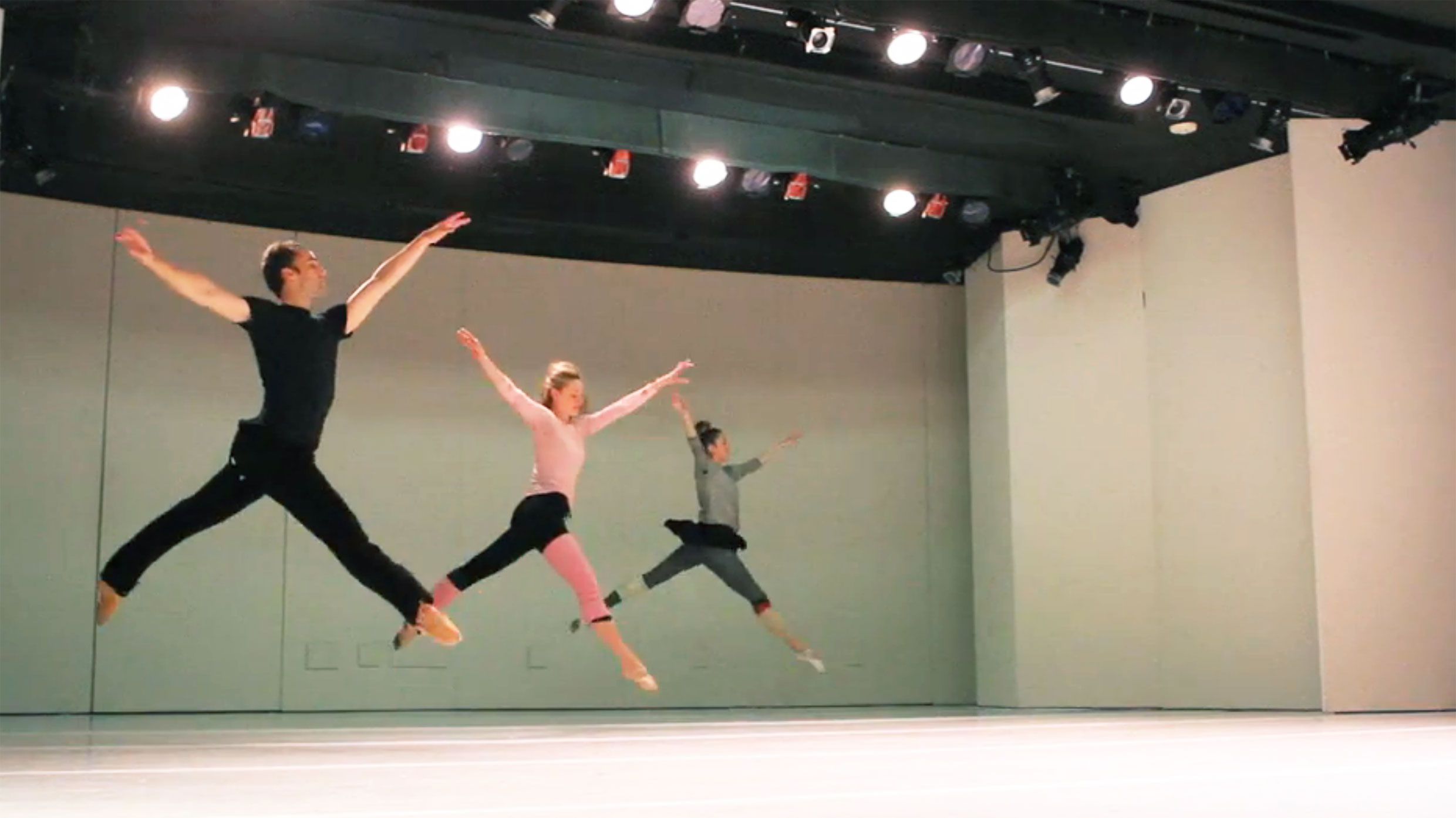 Dancers leaping across a stage. Photo: Jacklyn Meduga