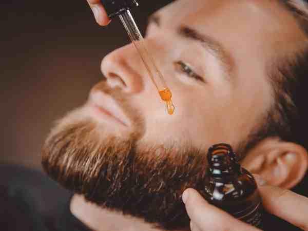 Homem aplicando óleo para barba.