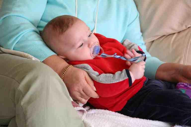 Imagem de bebê usando chupeta com suéter vermelh