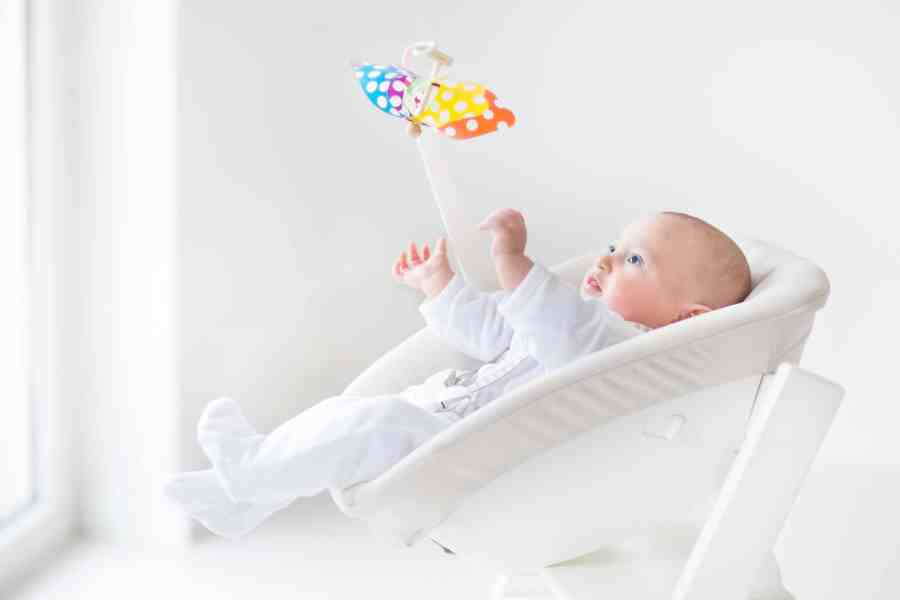 Bebê brinca e se distrai com barra de atividades de uma cadeirinha de descanso