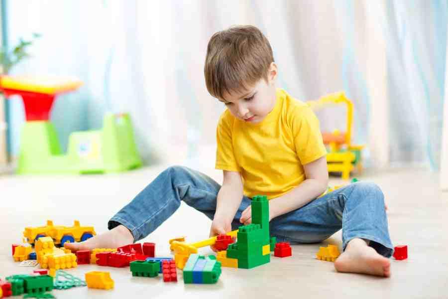 Imagem de menino sentado brincando com lego.