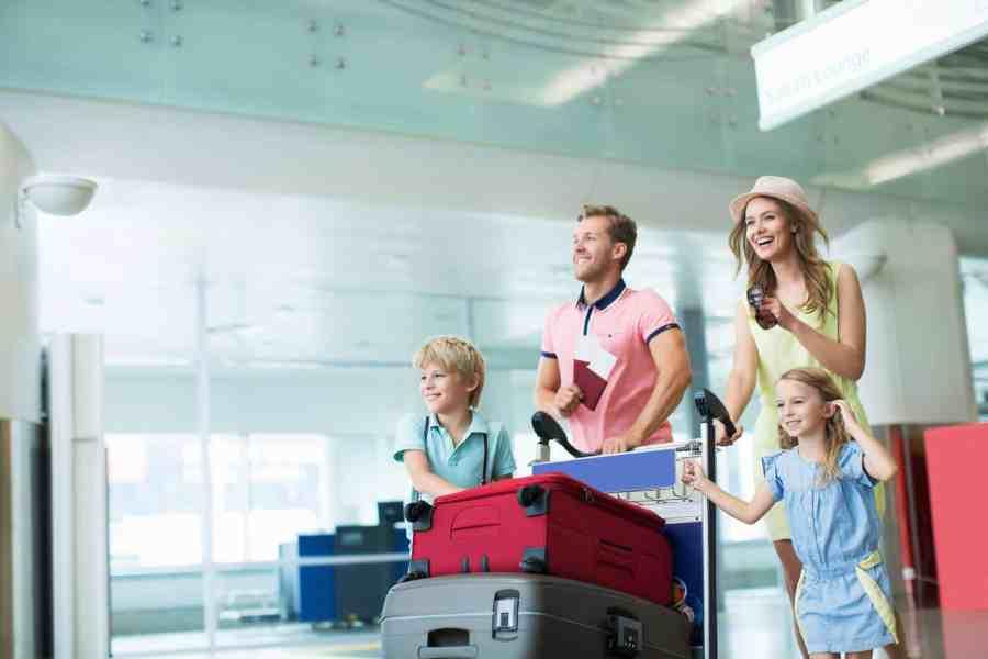 Imagem de família com malas em aeroporto.