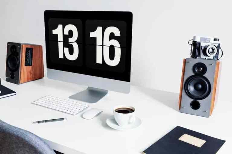 Imagem de mesa de escritório com computador e autofalantes.