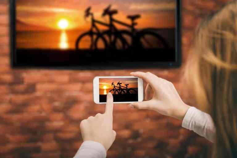 Imagem de pessoa tirando foto com smartphone de uma smart tv.