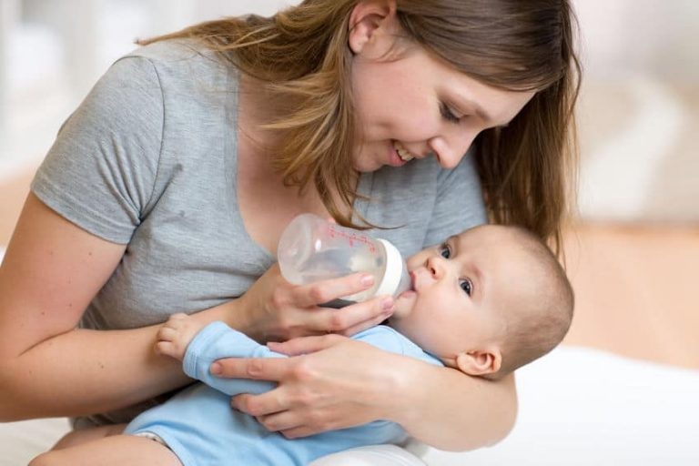 Mãe dando mamadeira para bebê.