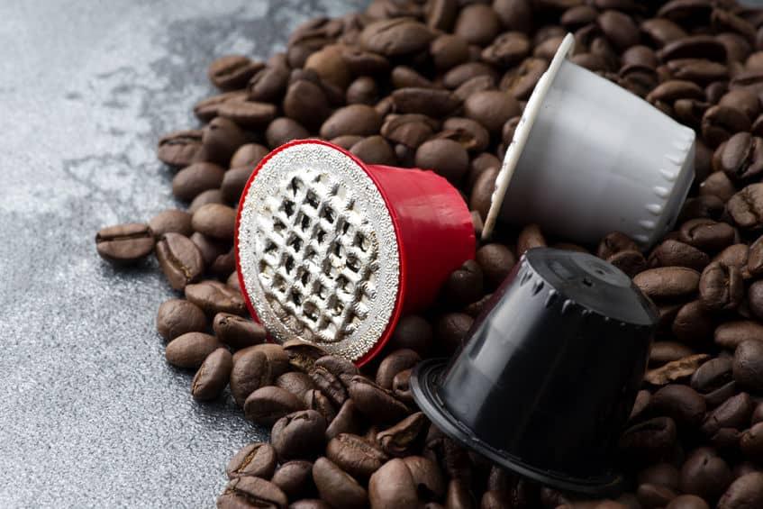 Grãos de café espalhados e três cápsulas de café