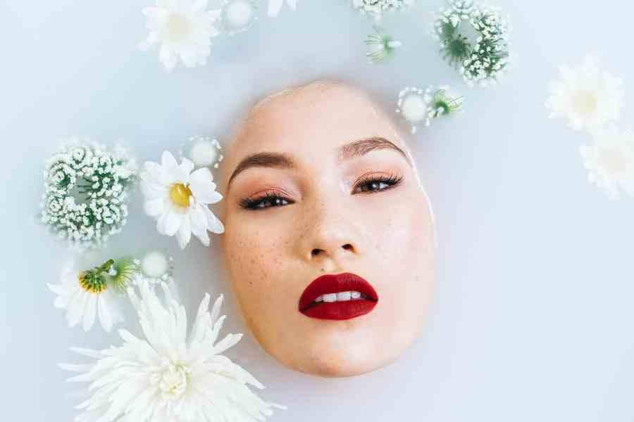 Mulher maquiada dentro de banheira.