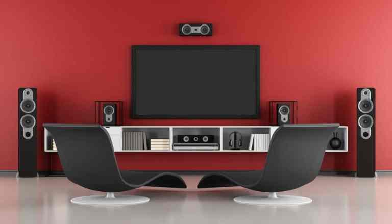 Imagem de TV em sala de estar com home theater em parede vermelha.