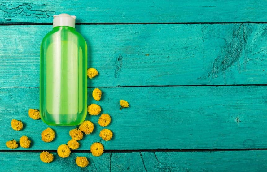 Fundo azul com frasco de cosmético e pequenas flores amarelas