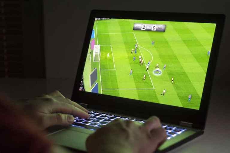 Pessoa jogando futebol com notebook gamer.