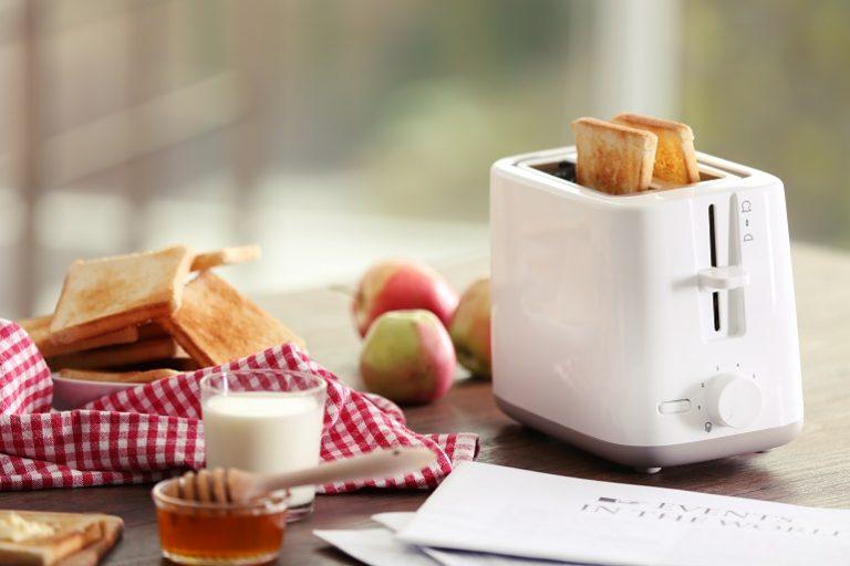 Pães na torradeira com outros alimentos de café da manhã ao lado.