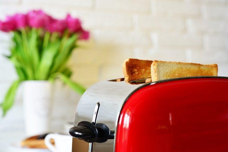 Torradeira vermelha com pães dentro.