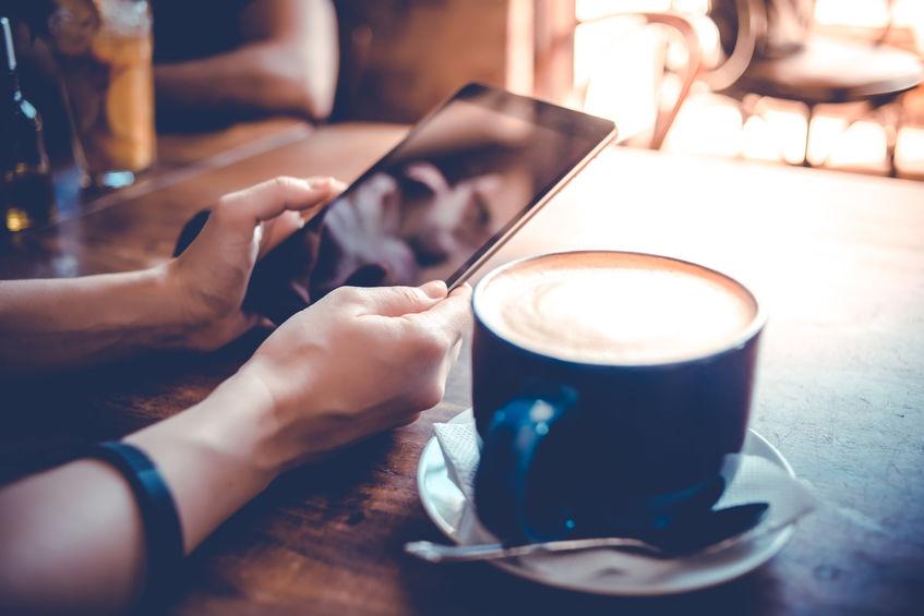 pessoa tomando café e usando um ipad