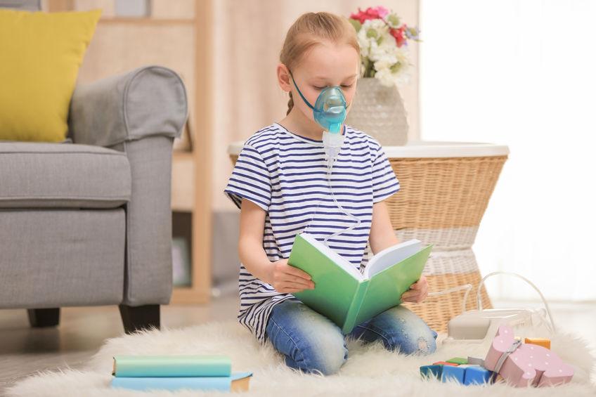 Menina usando máquina de asma em casa
