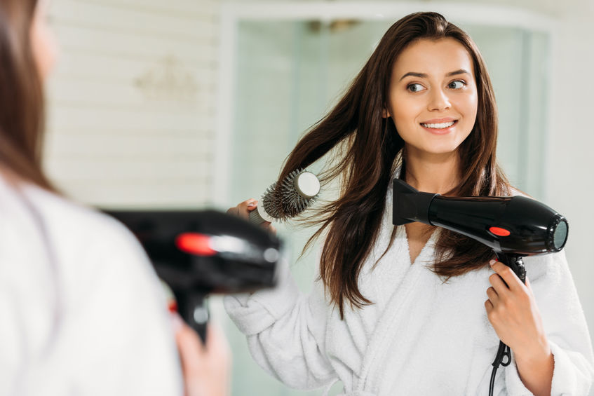 happy young woman drying hair at mirror in bathroom
