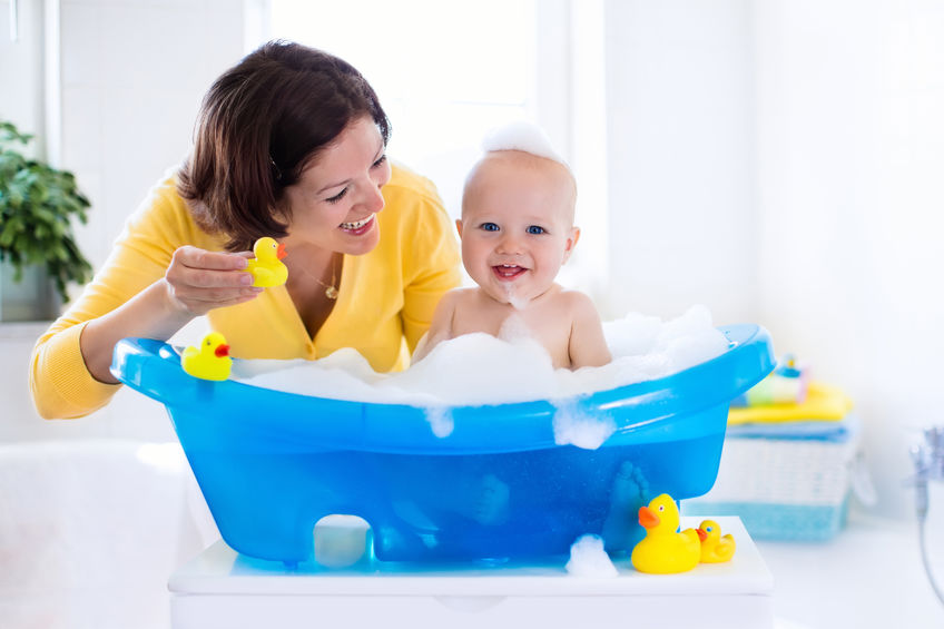Young mother bathing baby boy