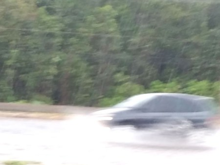 Carro passa sobre área alagada na EPTG, no DF (Foto: Inez Lopes/G1)