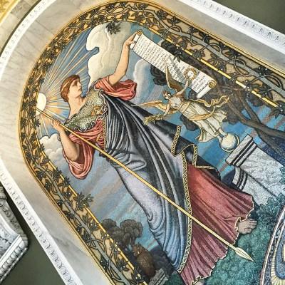 O Anjo da parede feito de mosaico com um papilo escrito em Latin no final Omnia mea mecum porto