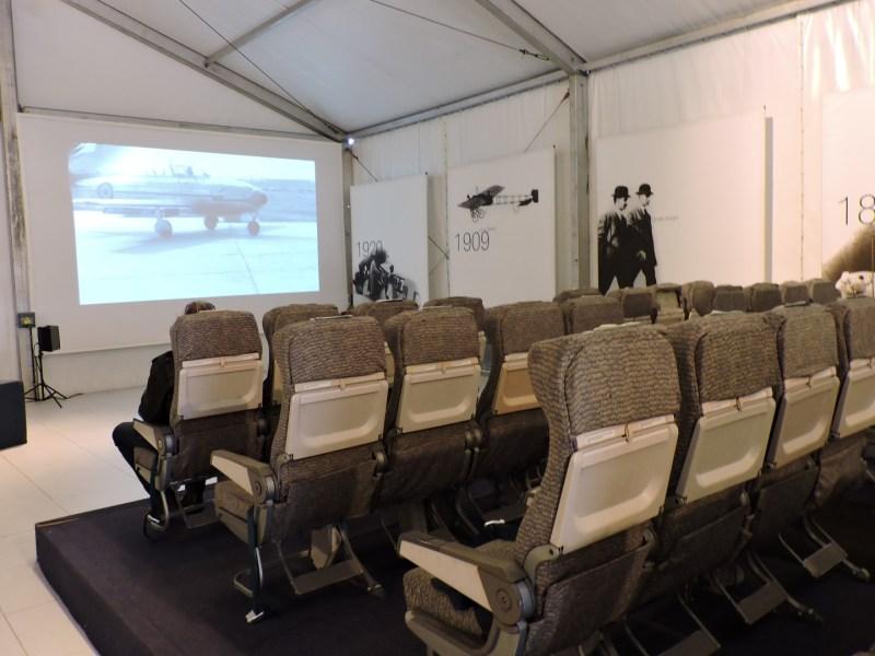 Museo del Aire - Zona de proyecciones, con asientos de un avión comercial.