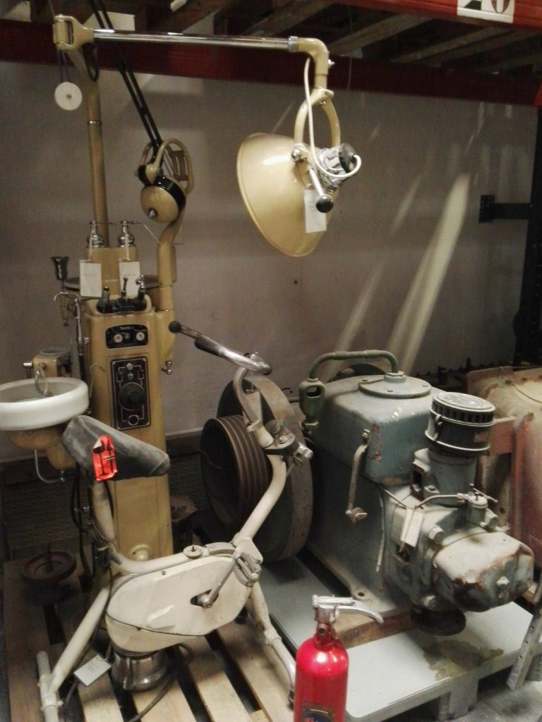 Almacén del MUNCYT - Un sillón de dentista, una Ciclostatic, un extintor y un compresor.