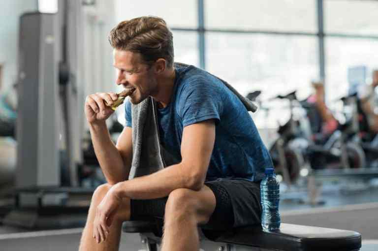 Hombre comiendo barra de proteína