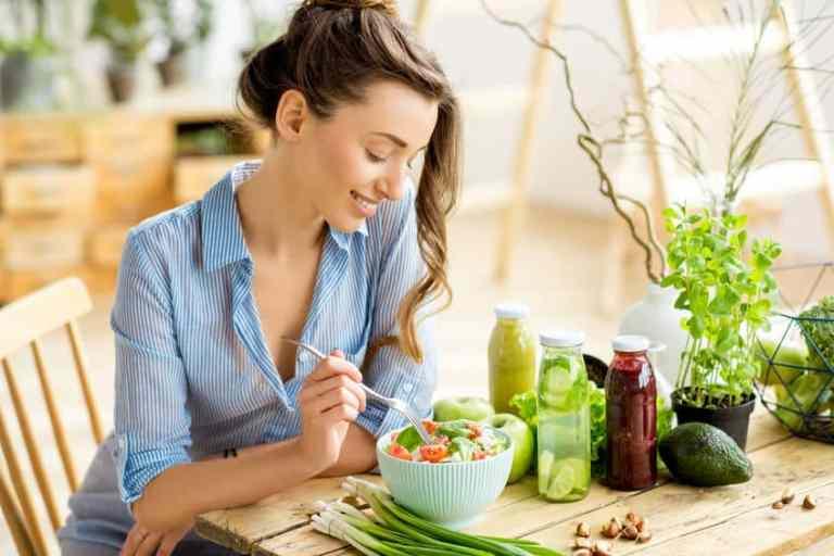 Mujer comiendo ensalada y tomando jugo
