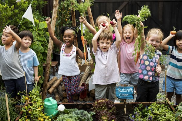 gruppo di bambini che fanno giardinaggio e si divertono tutti insieme