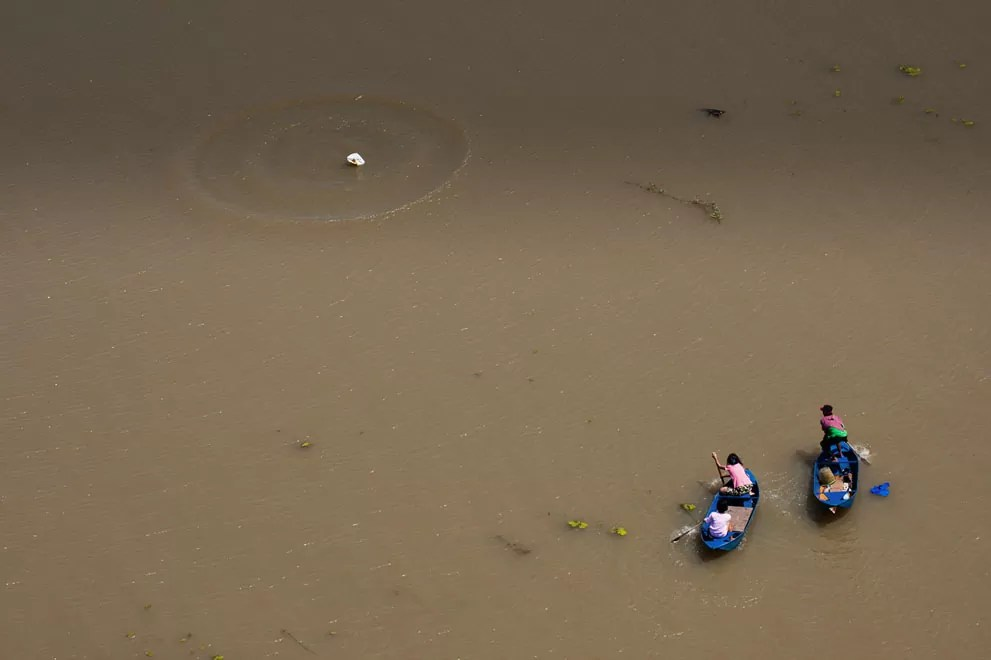 Des thailandais sur des barques lors des inondations près de Bangkok