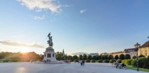 Reiterstandbild Erzherzog Karls auf dem Heldenplatz bei Sonnenuntergang, im Hintergrund das Rathaus, das Burgtheater und das Bundeskanzleramt