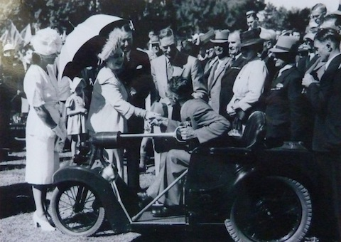 King George VI and Queen Elizabeth (later the Queen Mother) pictured with a Nelco Solocar. Who is the person in the driving seat?