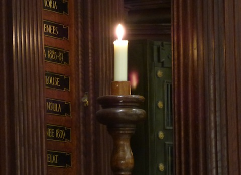 A candle burns in Holy Trinity Church at the memorial to The Queen's Regiment.