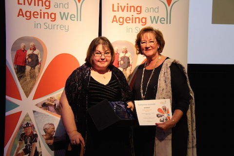 Catherine Jezierski receives her award from the chairman of Surrey County Council, Sally Marks.