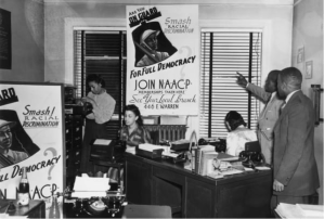 "A group of people pointing to a ""Join NAACP"" poster"