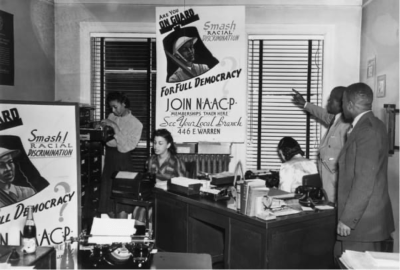 """A group of people pointing to a """"Join NAACP"""" poster"""