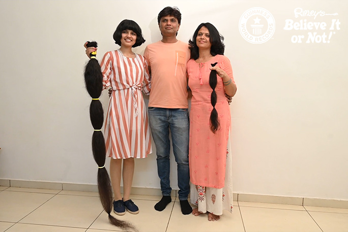 Nilanshi and her mum holding up her cut hair with her dad in the centre