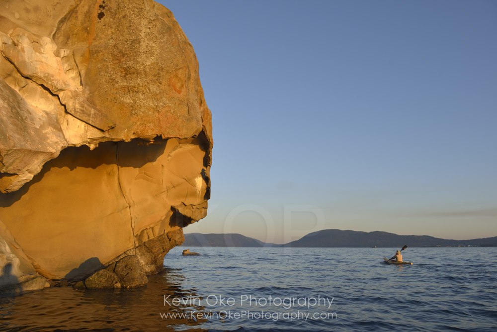 Sea kayaking under sculpted sandstone cliffs, Tent Island, Gulf Islands, British Columbia, Canada