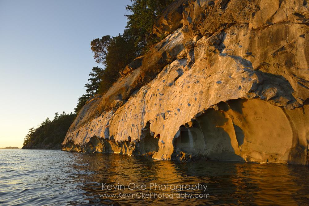 Sea kayaking under sculpted sandstone cliffs, Tent Island, Gulf Islands, British Columbia, Canada