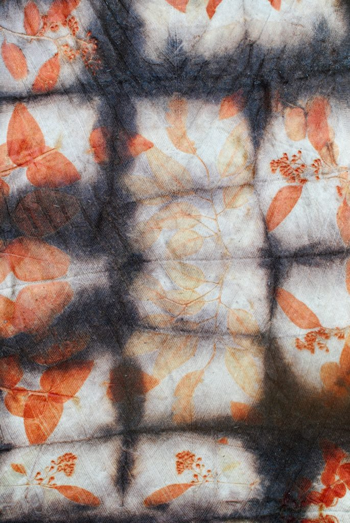 A piece of woollen fabric dyed with a dark grid, interspersed with bright orange leaf shaped prints