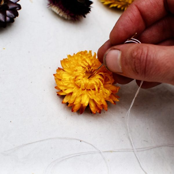 Fingers pushing a threaded needle through a paper daisy