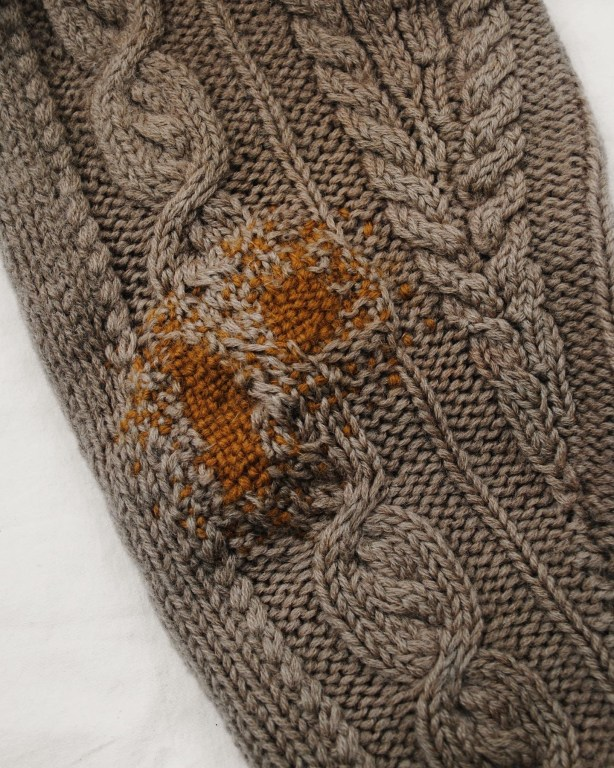 A close up of a cream coloured woollen knit sleeve with a cable pattern. Sections of the sleeve have been mending with golden yellow wool.