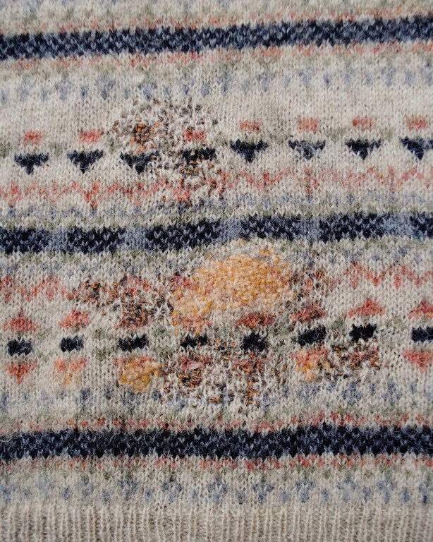 Close up of a patterned wool jumper, with sections of darning in contrasting colours.