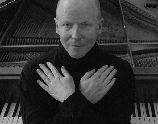 Gunnar Madsen hands crossed in front of piano