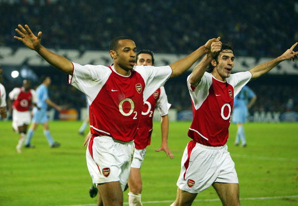 VIGO, SPAIN - FEBRUARY 24: Robert Pires of Arsenal (R) celebrates scoring their third goal with Thierry Henry during the UEFA Champions League match between Celta Vigo and Arsenal at Balaidos Stadium on February 24, 2004 in Vigo, Spain. (Photo by Phil Cole/Getty Images)