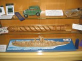 Displays 1929 Ford Model A, sugar sifter, bed post, and USS New Jersey.