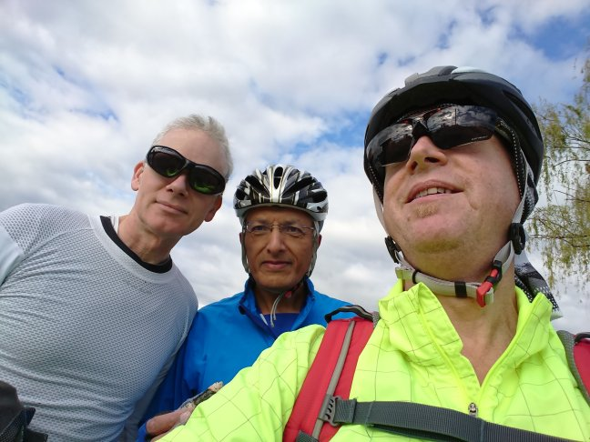 Selfie of three bikers in helmets and sunglasses