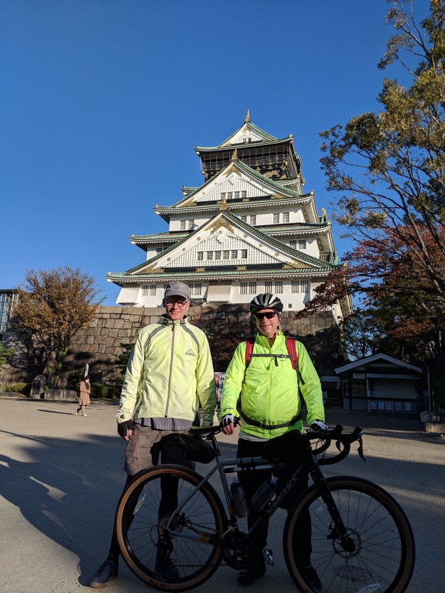 Two bikers standing in front of Osaka Castle