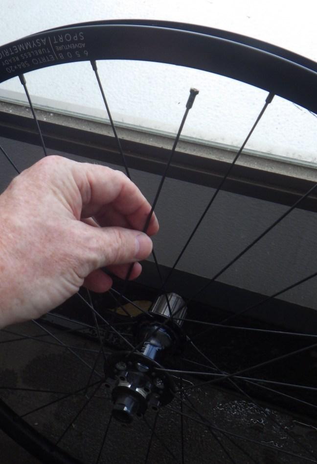 Bicycle spoke being measured against wheel