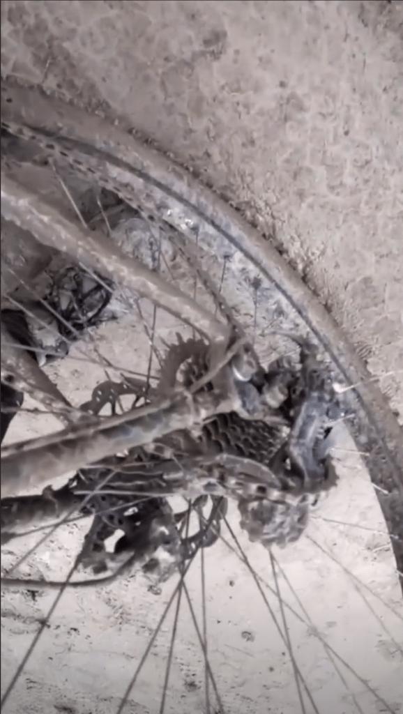 Muddy bike wheel with broken derailleur